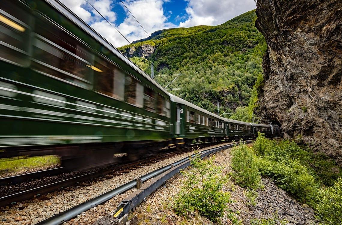 Grønt tog som kjører inn i en tunnel